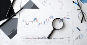 A magnifying glass over charts related to finance - CTA Advogados